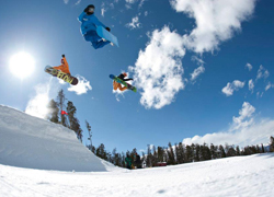 3 snowboarders hitting a jump